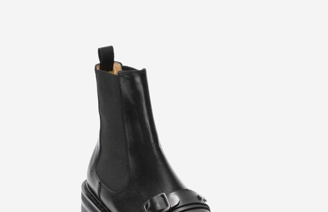 Black calf leather Chelsea styled buckled boot with functional elastic inserts and a leather back pull. The boot features a leather strap with a buckle and is finished with a black chunky rubber tank sole with an Alexander McQueen signature underneath.