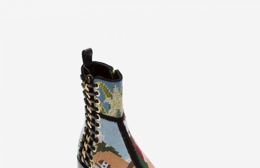 Black suede boot features an exaggerated pointed toe, a signature silver metal braided chain and leather lace with hand-applied eyelets. The multicolor tapestry patchwork embroidery is derived from the RTW collection. The boot is finished with an embossed Alexander McQueen signature on the leather sole.