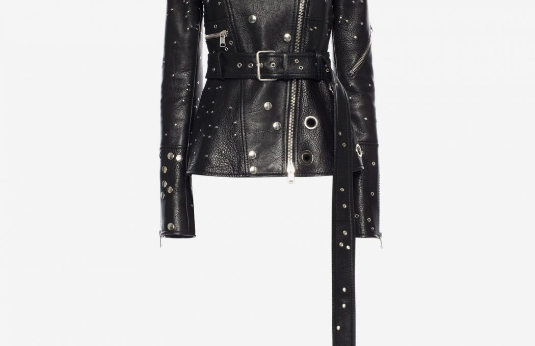 Black studded biker jacket in a natural grainy buffalo leather, featuring a double ended metal zipper and snap fastening. All-over silver plated metal stud embellishment. Finished with a waist belt and quilted silk lining.