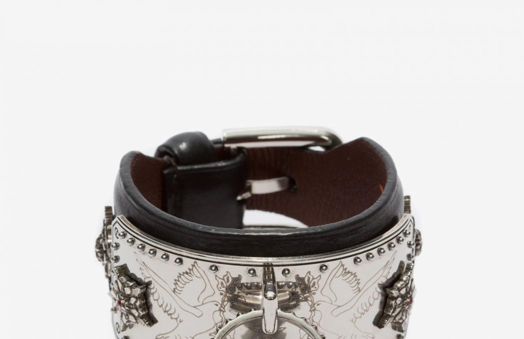 Black lambskin leather Padlock cuff with an engraved silver metal plate and a fully functioning engraved lock. The cuff features Swarovski crystals and faux pearls. Adjustable buckle closure.